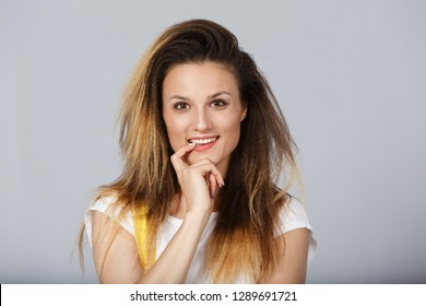 Headshot of tricky beautiful woman with curly long-hair style touching lips, looking at camera with cunning smile and having some ideas in her mind. Attractive female having sly expression