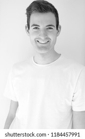 Headshot a white man in a t-shirt against a white background smiling looking at camera. Fit and healthy man posing for the camera. Happy man smiling, black and white.