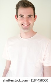 Headshot a white man in a t-shirt against a white background smiling looking at camera. Fit and healthy man posing for the camera. Happy man smiling.