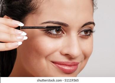 headshot woman applying mascara
