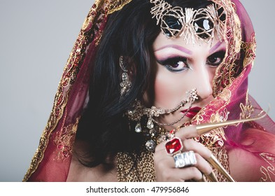 Headshot woman dressed in traditional hindu clothing, heavily decorated in gold and elegant veil, extremely long fingernails, posing artistically for camera, hindusim dancer concept