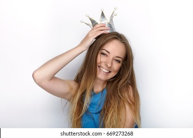 Headshot of young adorable blonde woman with cute smile in hand made princess crown on white background