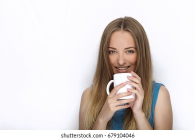 Headshot of young adorable playful blonde woman with cute smile in cobalt color blouse posing with big pure white mug on white backdrop