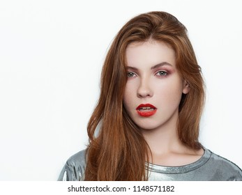 Headshot of young beautiful excited woman with gorgeous natural red hair, red lips, green eyes in glossy silver blouse on white background