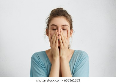 Headshot of young beautiful student female closing her eyes holding hands on chin being tired after hard work trying to relax for a minute and to gather her thoughts. Tiredness, feelings concept