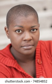 Headshot of a young black woman with a shaved head