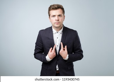 Headshot of young european man in suit pointing at himself, making excuses or verbally defending, having perplexed and puzzled look. You mean I am wrong concept