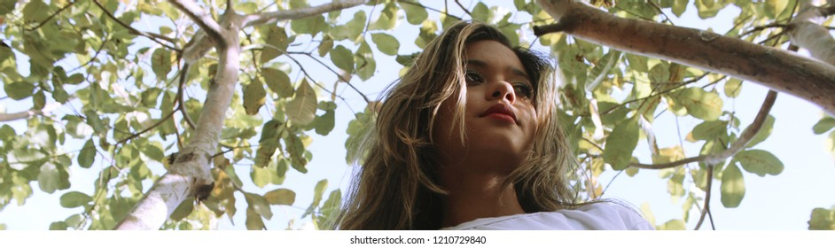 Headshot of young female model, seen from below, with top of trees on background