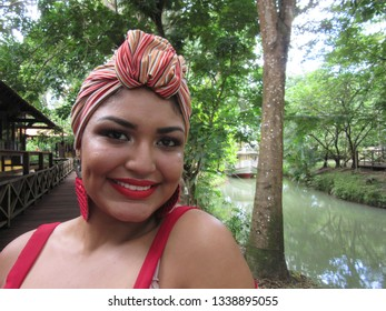 Headshot of young female model with turban, in park, near a waterway