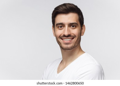 Headshot of young handsome european caucasian man wearing casual white t-shirt, smiling happily and friendly at camera, isolated on gray background