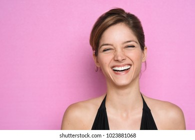 Headshot of young pretty woman in black dress posing on pink and laughing happily.
