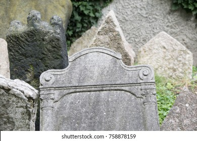 Headstone with carved swirls and iconic columns, name worn off. Very old cemetery with a group of weathered and worn out gravestones. Group of old stone headstones in a graveyard, no names on graves.