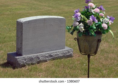 Headstone in a cemetery is decorated with flowers in memory of a loved one lost.