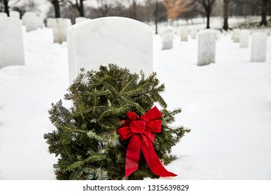 Headstone in a cemetery with a wreath made out of pine branches in the winter with snow on the ground