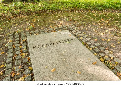 The headstone of the famous danish writer Karen Blixen, with yellow autumn-leaves.  The tomb is in the park of her home Rungstedlund, Denmark, october 10, 2018