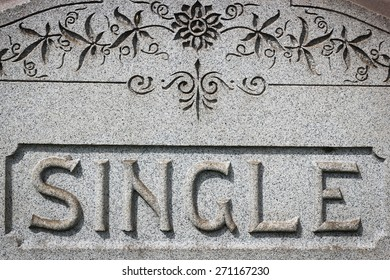 """Headstone with the word """"Single"""" carved in stone with ornate decorative pattern above the word"""
