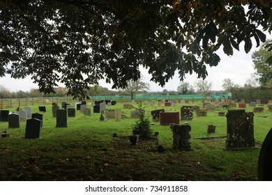 Headstones in churchyard with trees and flowers