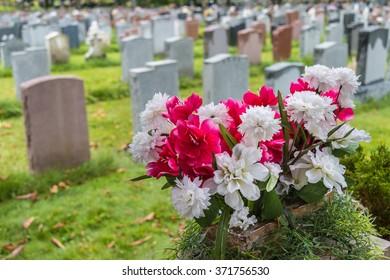 Headstones on a graveyard in Fall with flowers in the foreground, in an american cemetery