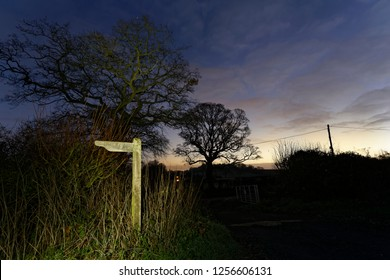 Headtorch lights up a footpath sign and distant oak tree in the early dawn sunrise Oakley Hampshire