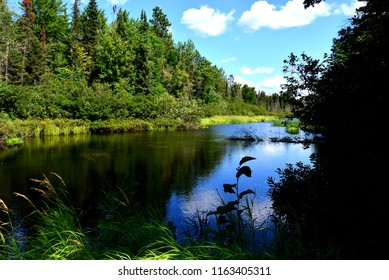 The headwaters of the Wisconsin River by Land O Lakes, Wisconsin with deep blue reflective water and clouded sky.