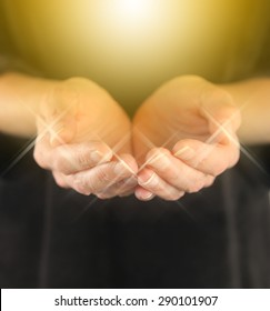 Healer with Golden Healing Orb Energy - female holding hands in cupped position with a bright golden orb  energy hovering above and sparkles around finger tips