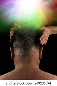 Healer working on Crown Aura Energy - Back of a man's head with female hands hovering either side on a black background with an ethereal colorful burst of light above in the crown chakra area