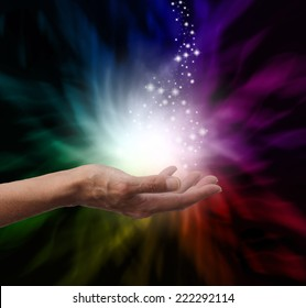 Healer's hand outstretched into magical healing energy field with sparkles and rainbow colors on a black background