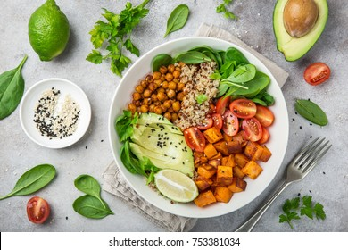 healhty vegan lunch bowl with ingredients. Avocado, quinoa, sweet potato, tomato, spinach and chickpeas vegetables salad. Top view
