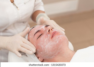Healing Care Cream after Laser rejuvenating facial face treatment at cosmetology clinic. Young woman getting lifting anti-aging and skincare, laser polishing facial therapy, aesthetic cosmetology.