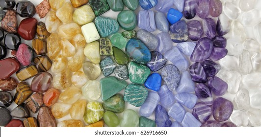 Healing Chakra Crystals Banner - Chakra colored tumbled healing stones laid in neat color coordinated rows creating a crystal healing background