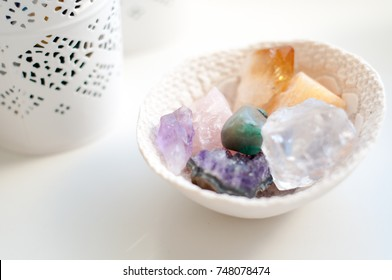 Healing crystals on a white table including: Amethyst Point and Cluster, Agate, Aventurine, Clear Quartz, Citrine, Calcite and Rose quartz. Gemstones are full of healing energy and good vibes.