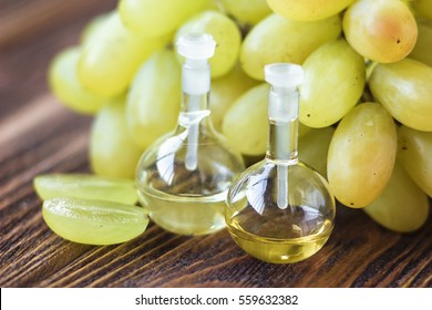 Healing grapes seeds oil in a glass jar, fresh grapes on old wooden background, seed extract has antioxidant and nourishing the skin, spa concept, selective focus macro front view. Bio, eco products.