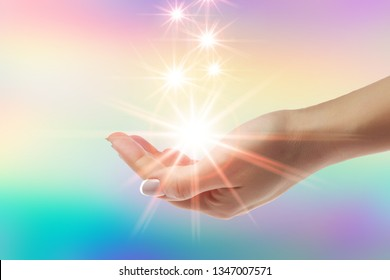 Healing hands with bright sunburst on rainbow background