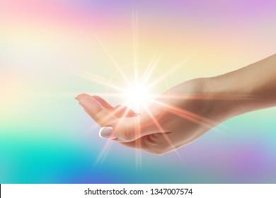 Healing hands with bright sunburst on rainbow background