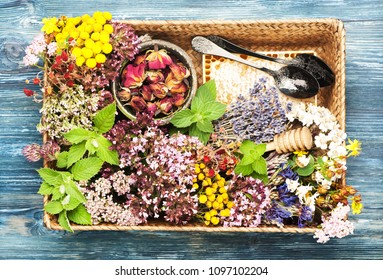 Healing herbs and flowers for herbal tea and honeycomb in a tray  on a blue wooden background, top view, flat lay