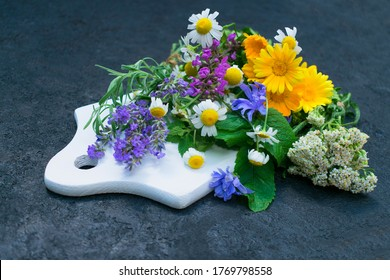 Healing herbs and flowers on a white wooden board. The concept of natural cosmetics.