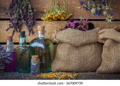 Healing herbs in hessian bags, bunches of medicinal herbs and bottles of tincture or oil, herbal medicine.