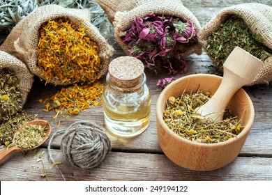 Healing herbs in hessian bags, mortar with chamomile and essential oil on wooden table, herbal medicine.