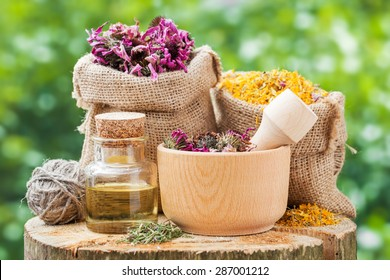Healing herbs in hessian bags, wooden mortar with coneflowers and essential oil on wooden stump outdoors, herbal medicine.