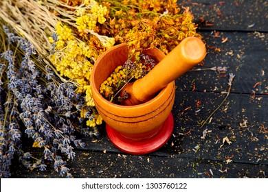 Healing herbs on wooden black table, herbal medicine. tutsan, sagebrush, oregano, helichrysum lavender