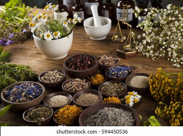 Healing herbs on wooden table, mortar and herbal medicine