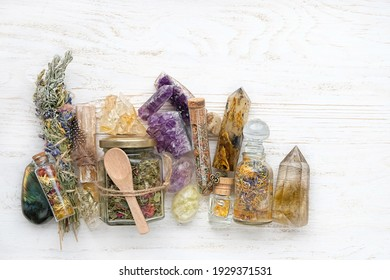 Healing mineral gemstones, herbal tea in jar, spell bottles on rustic white table. witchcraft things for Self-Care Ritual. flat lay