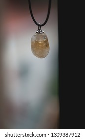 Healing stone necklace with a mineral quartz pendant on the blurred background with copy space, meditation concept, healing concept, yoga concept