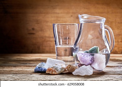 Healing stones, colorful marble minerals in transparent water in glass jug and on rough wooden table surface. Alternative medicine concept with copy space