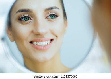 Health and Beauty. Beautiful Young Girl With Clean Skin Looking In The Mirror. Beauty and Care. Portrait of a Young Woman