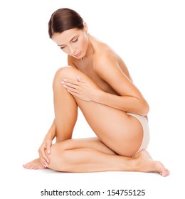health and beauty concept - beautiful naked woman touching her legs