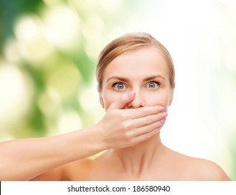 health and beauty concept - clean face of beautiful young woman covering her mouth with hand
