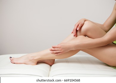 Health and beauty concept. Close up of girl's legs on couch. Girl touching her soft and smooth legs after laser epilation or depilation.