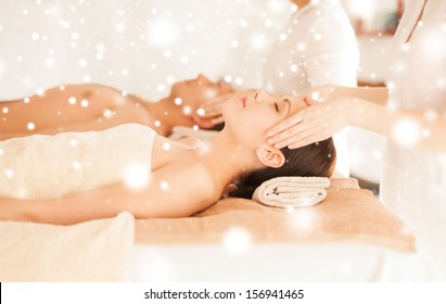 health and beauty concept - couple in spa salon getting face treatment