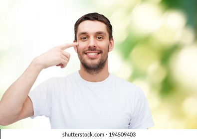 health and beauty concept - smiling young handsome man pointing to eyes